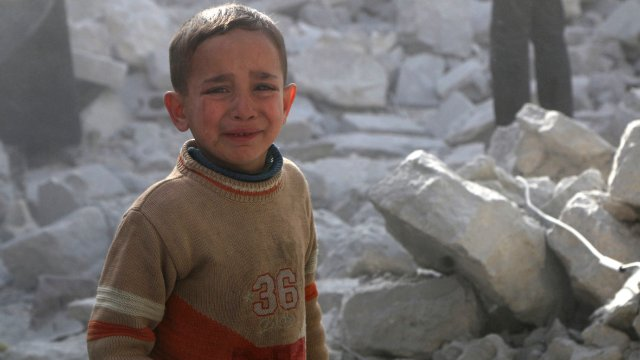 A boy cries as he stands amid rubble of collapsed buildings at a site hit by what activists said was a barrel bomb dropped by forces loyal to Syria's President Bashar al-Assad in Aleppo's al-Sakhour district