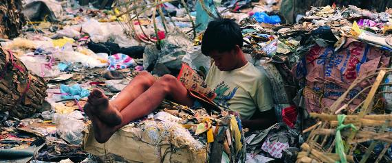 Young boy reading comic on Smokey Mountain, Manila, Philippines